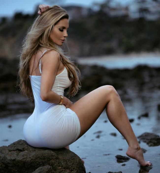 Аманда Ли фото сидящей на камне у воды в белом коротком платье, шикарная попа, ножки, ступни