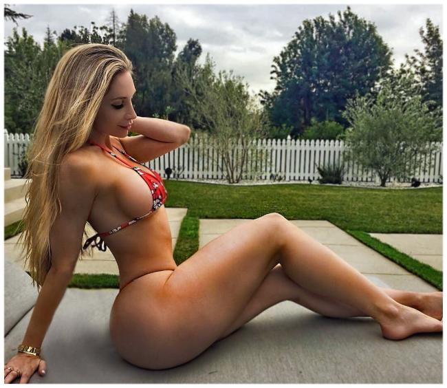 Аманда Ли горячее фото сидит на попе на газоне в купальнике бикини еле прикрывающем ее сексуальное тело, ноги немного согнуты в коленях, вид сбоку