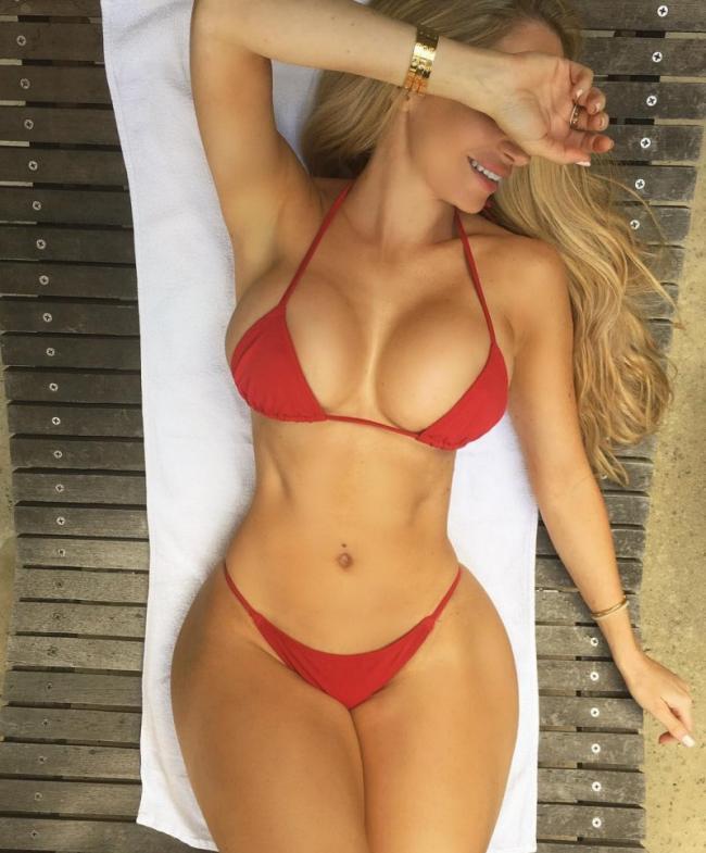 Аманда Ли горячее фото лежит на пляже в красном купальнике бикини, правой рукой прикрыла глаза, улыбается