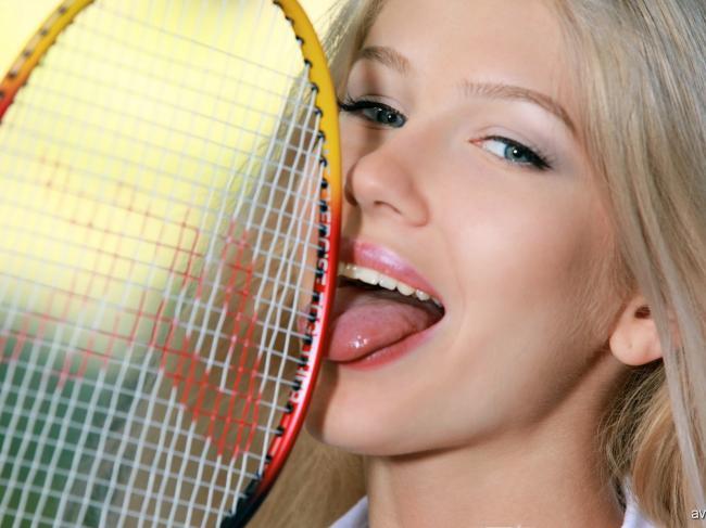 Красивая молодая блондинка эротично облизывает ракетку для бадминтона.