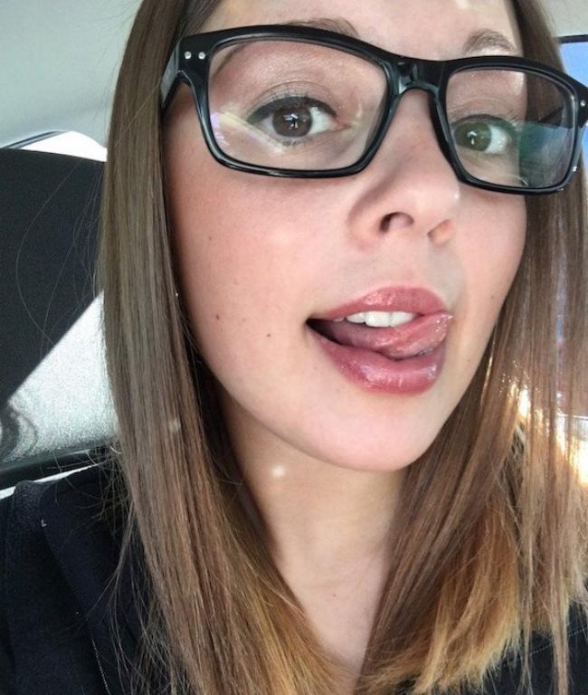 девушка в сексуальных очках показывает язык, эротично водит по губам фото
