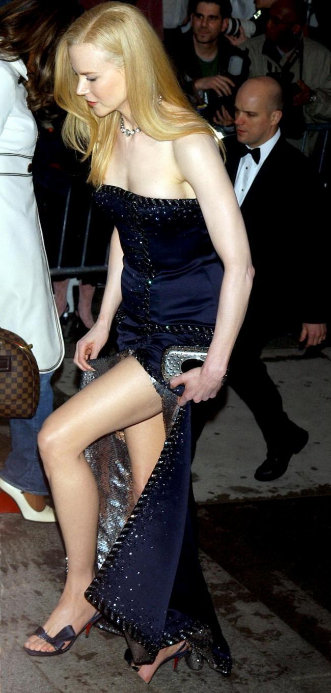 Поднимается по лестнице в красивом вечернем платье оголяя прелестные ножки.