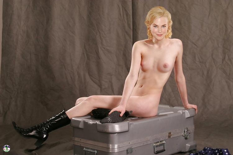 Голая в черных сапожках сидит на чемодане.