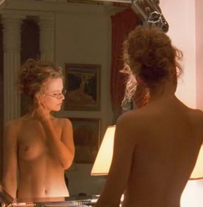 Голая Николь в очках возле зеркала.