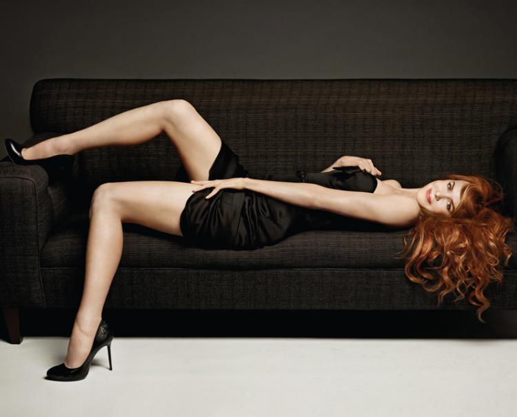Лежит на черном диване в черном коротком платье черные туфли на соком каблуке.