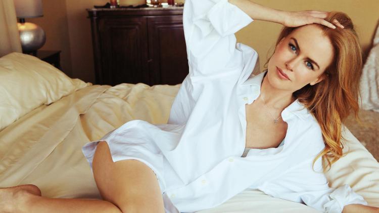 Лежит на кровати в белой рубахе.