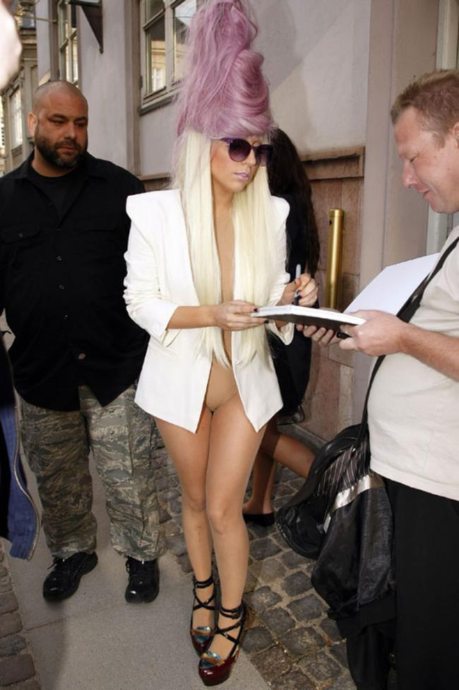 Леди Гага фото в полный рост в белом пиджаке с прической в виде пирамиды делает запись в книге отзывов