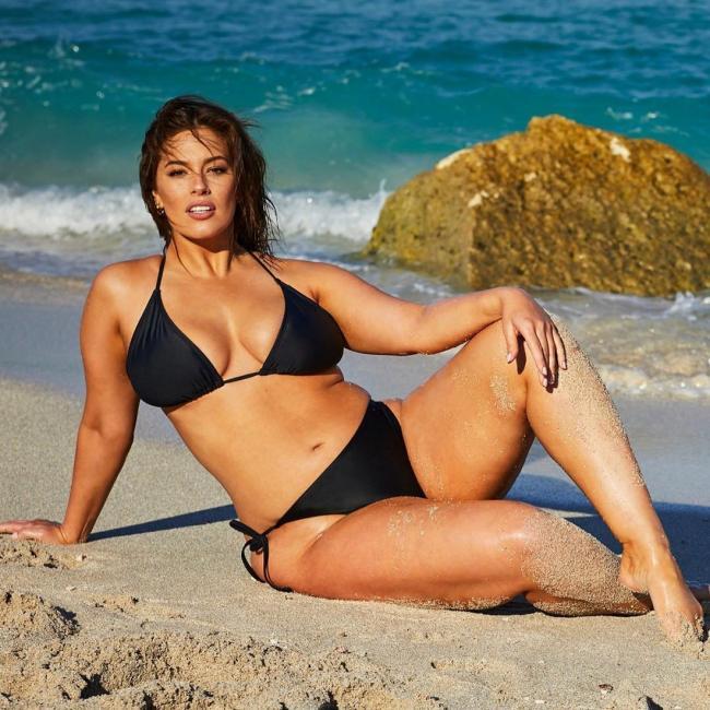 В черном бикини сидит на песке.