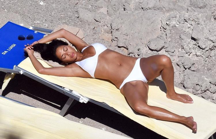 В белом купальнике загорает на солнце подняв руки раздвинув ноги.
