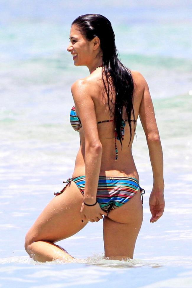Николь Шерзингер стоит по колено в море океане попровляет бикини на попе