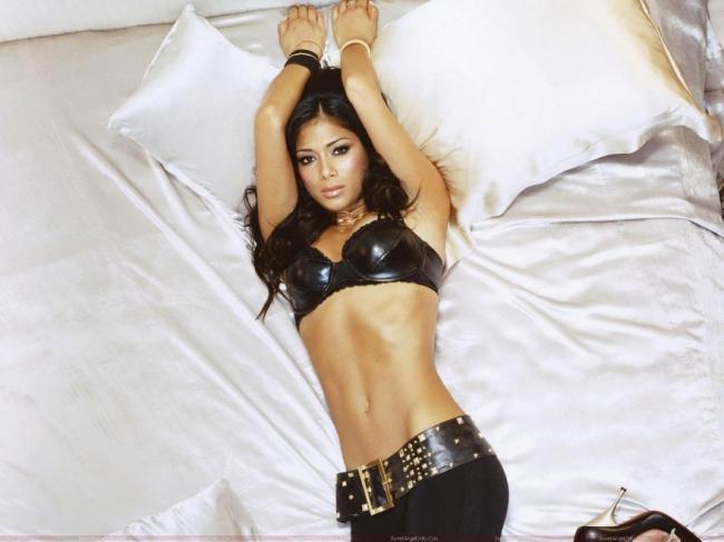Николь Шерзингер в латексе подняв связанные руки лежит на кровати
