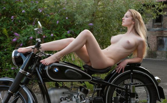 Голая блондинка с длинным волосами лежит на мотоцикле ножки на руле