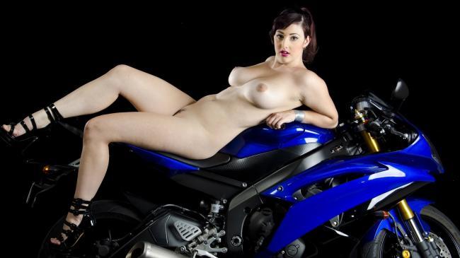 сочная брюнеька с шикарной грудью лежит на мотоцикле.