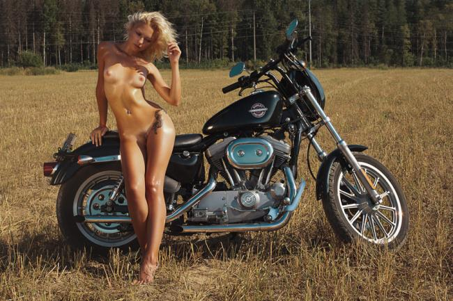 Блондинка голая в поле возле мотоцикла стоит.