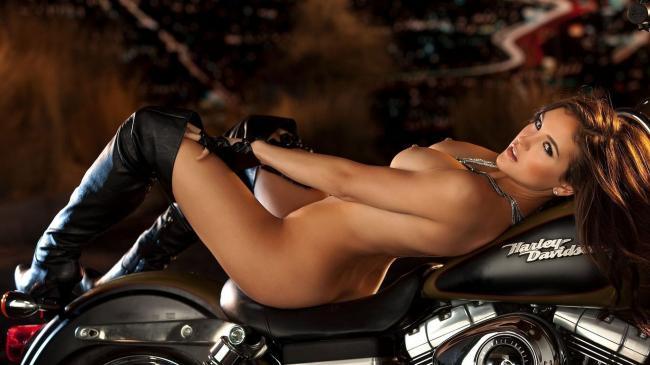 Шикарная красотка голая в ботфортах лежит на Harley черного цвета.