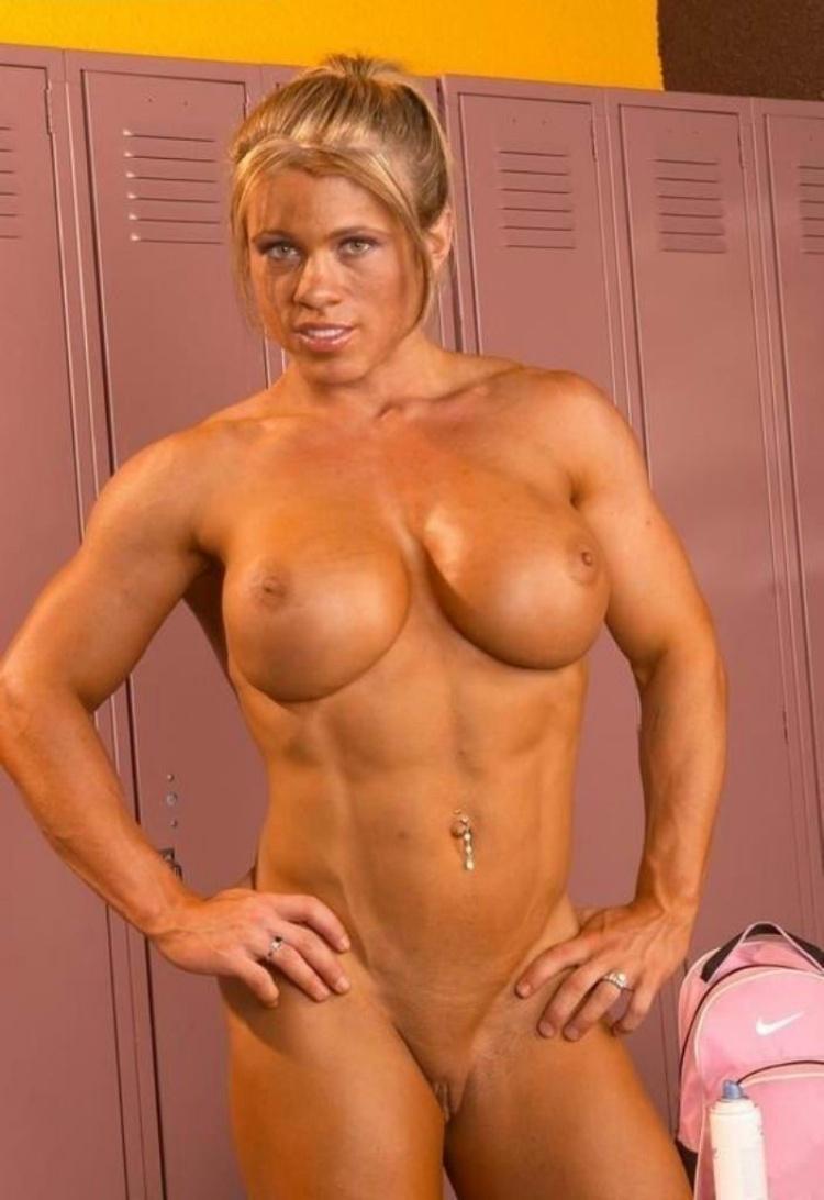 Голая накаченная блондинка стоит в раздевалке руки на бедрах в пупке пирсинг пизда бритая