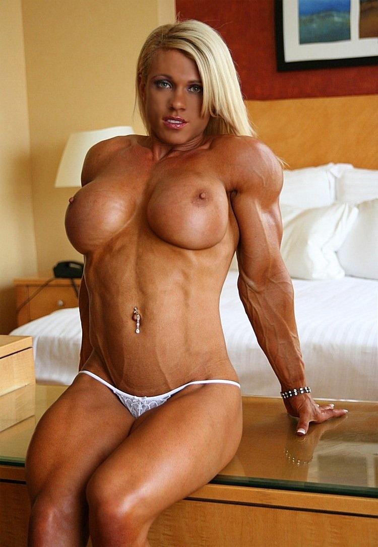 Голая накаченная блондинка сидит на краю кровати с накаченными сиськами в белых стрингах улыбается