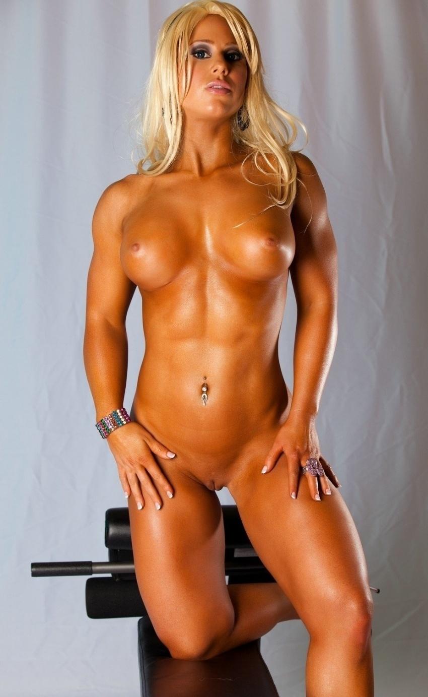 накаченные телки красивая голая блондинка с пирсингом в пупке стоит возле тренажера