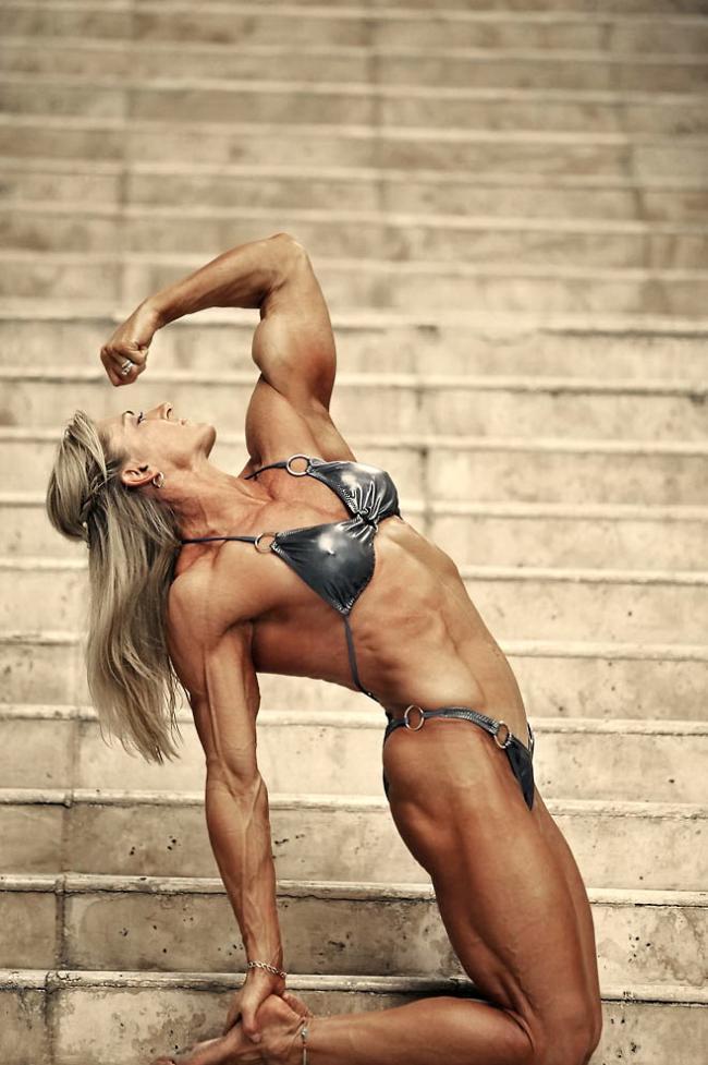 накаченная блондинка в серебристом купальнике стоит на коленях демонстрируя сою фигуру