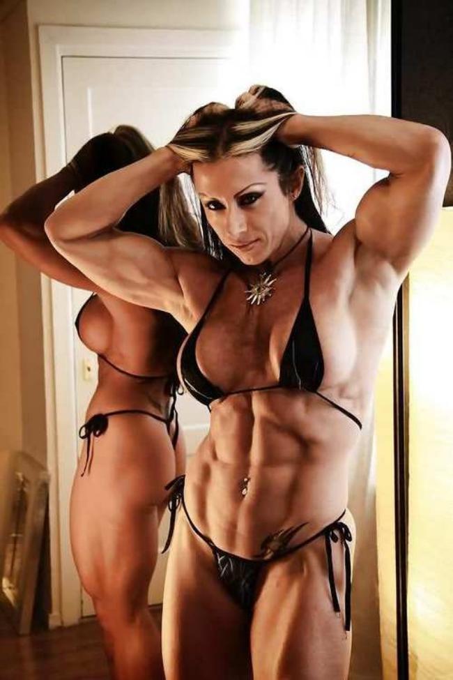 Накаченная телка в мини бикини купальнике стоит у зеркала демонстрируя мышцы своего тела в пупке пирсинг