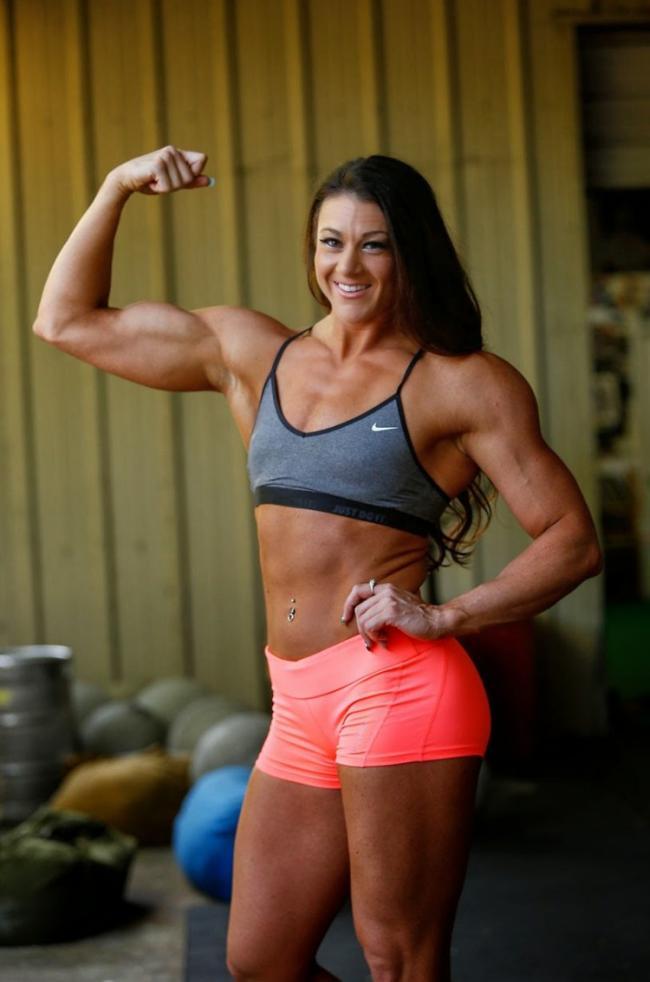 Накаченная зрелая в ярких шортах и коротком топике демонстрирует свои мышцы