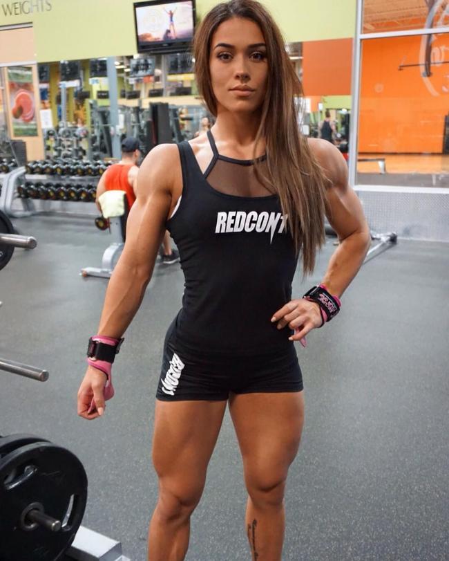 Красивая накаченная телка стоит в спортзале с длинным распущенным русым волосом