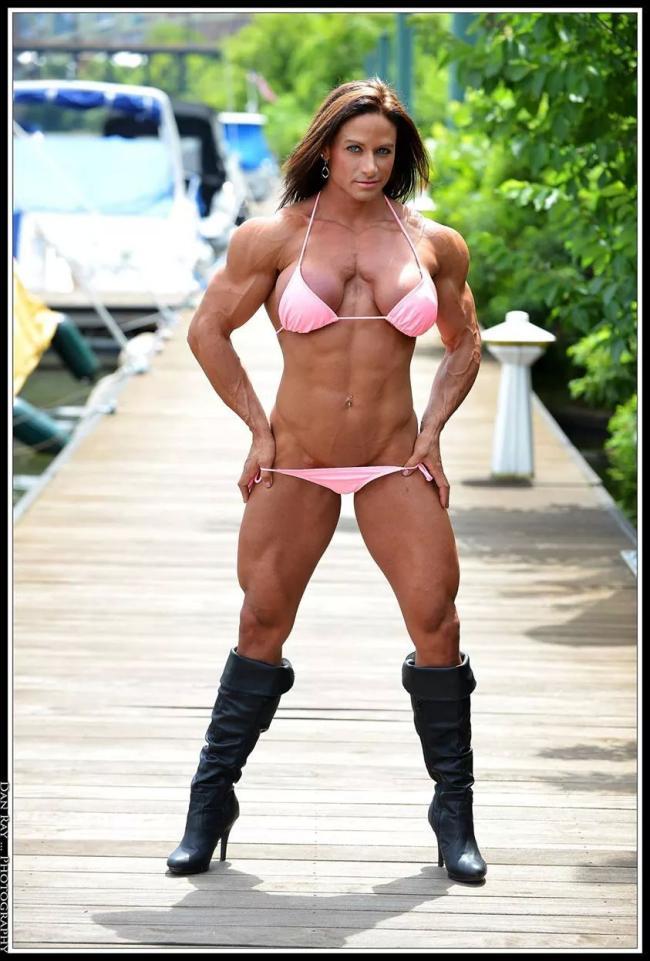 телка +с накаченными ногами бицепсами и плечами в розовом купальнике и черных сапогах на высоком каблуке стоит на пирсе