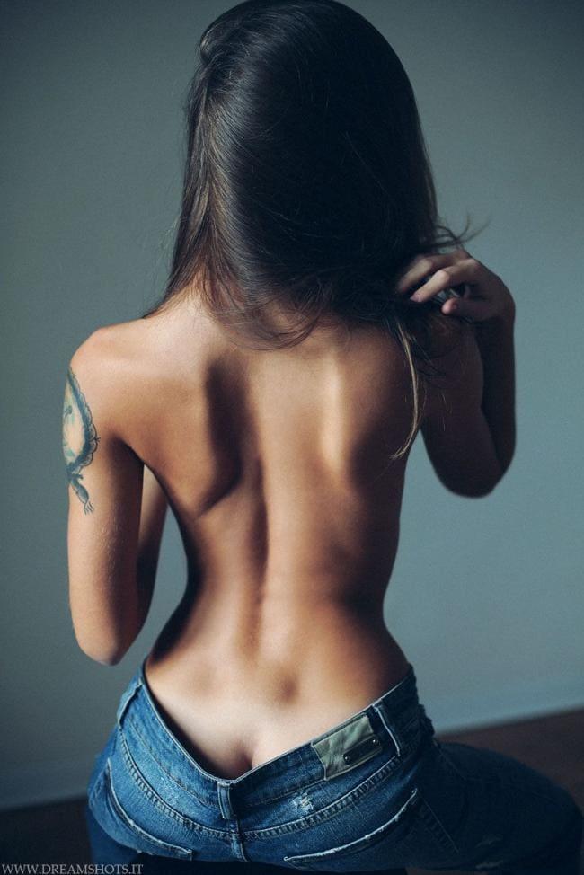 Спина девушки, татуировка на плече.