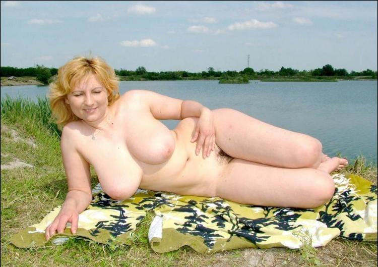 Голая тетка с большими сиськами лежит на коврике у реки.
