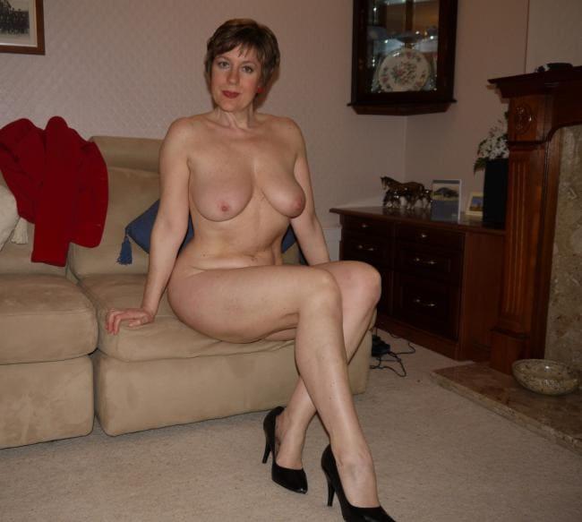 Зрелая тетка с короткой стрижкой сидит голая на диване в черных туфлях на высоком каблуке
