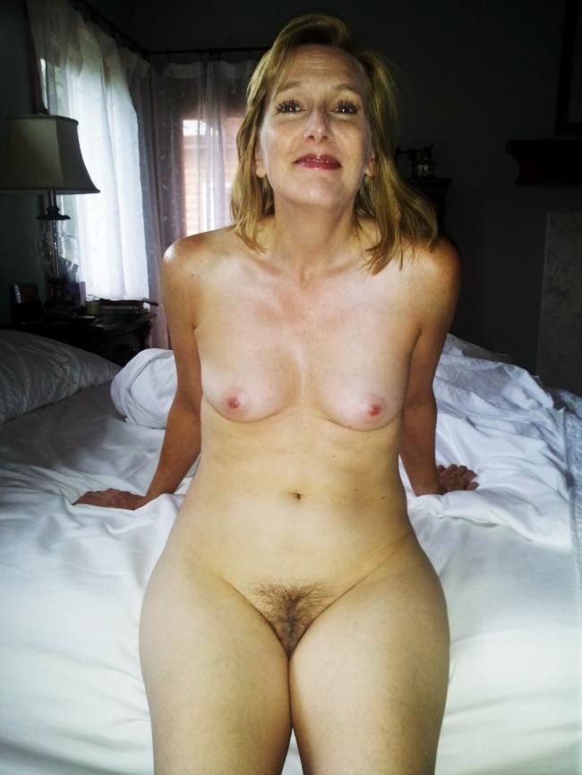 Голая дама сидит на кровати с мохнатой кисей.