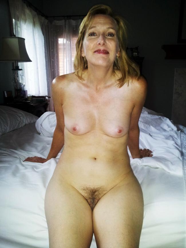 Голая зрелая тетка сидит на кровати с мохнатой кисей
