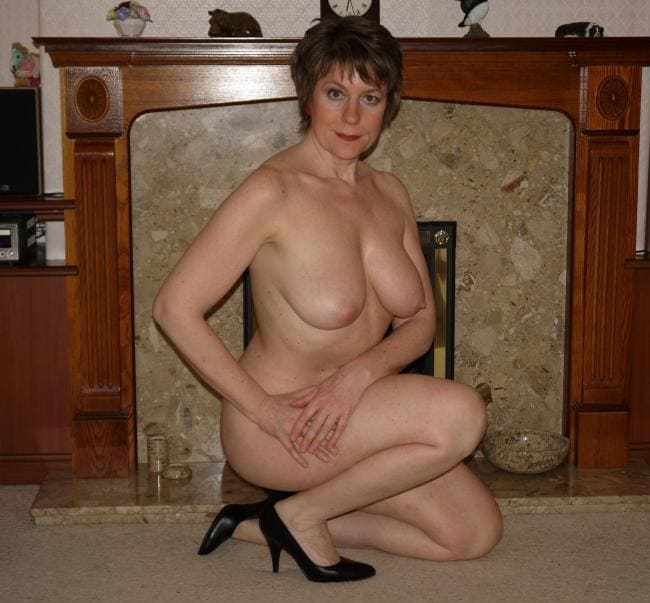 Зрелая голая тетка сидит на корточках у камина