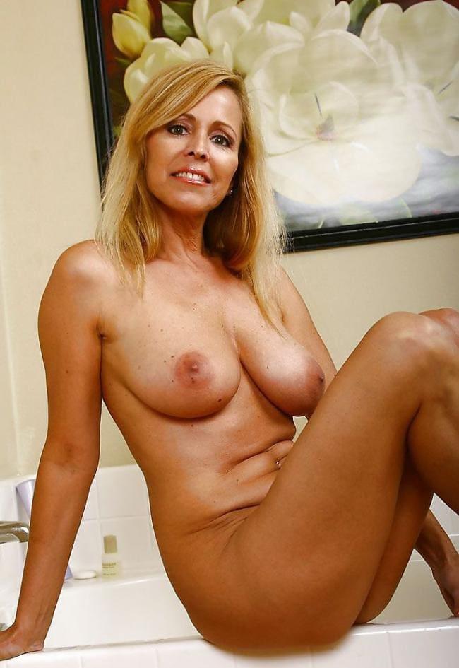 Шикарная загоревшая зрелая блондинка сидит на ванной.