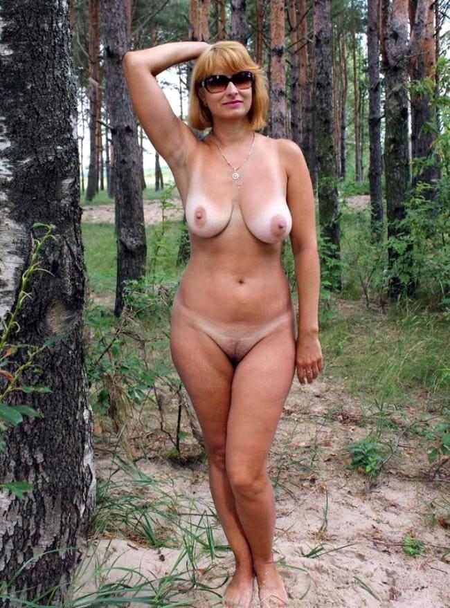 Зрелая блондинка голая стоит в лесу.