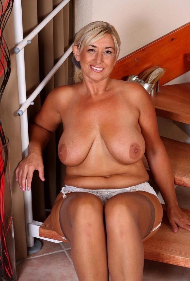 Голая блондинка сидит на ступенях большая грудь.