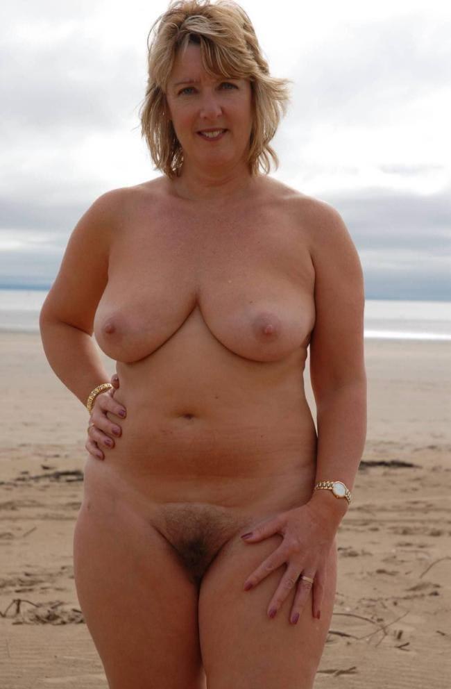 Полненькая голая блондинка на пляже.