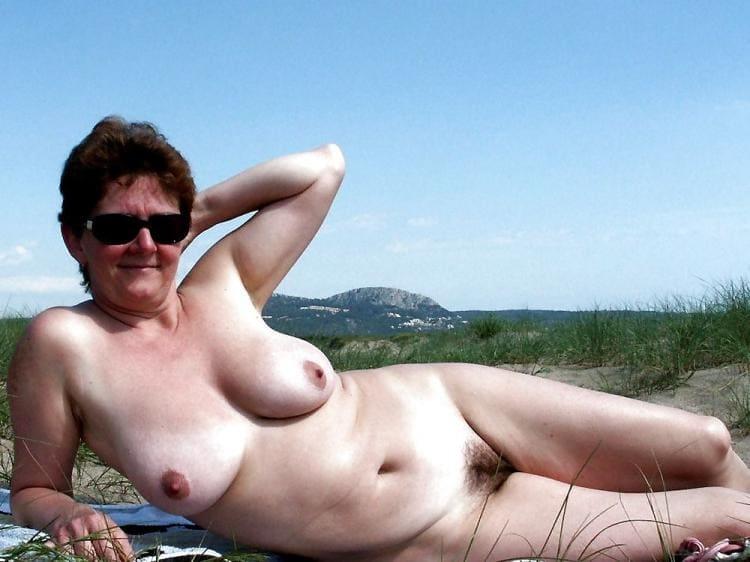 Голая тетка с мохнатой писей лежит на травке подняв руку.