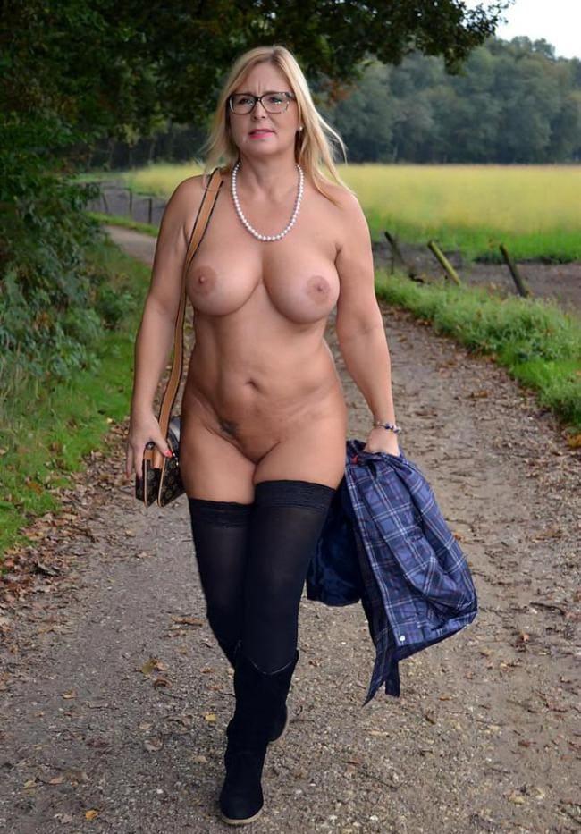 Голая зрелая блондинка идет по дороге в ботфортах.