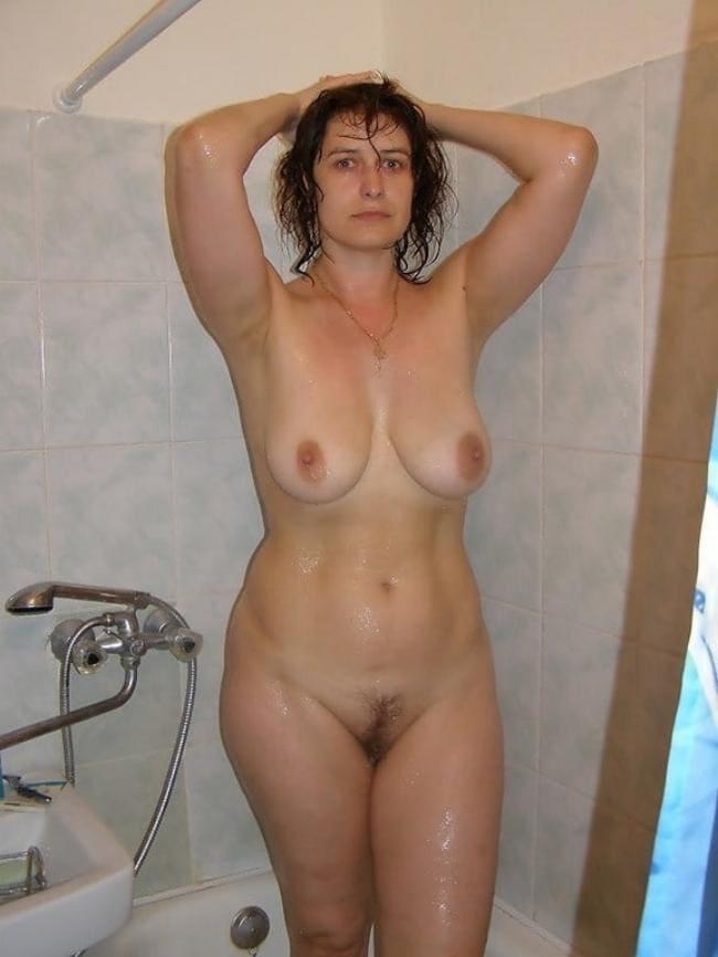Зрелая тетка стоит в ванной мокрая и голая , руки на голове.