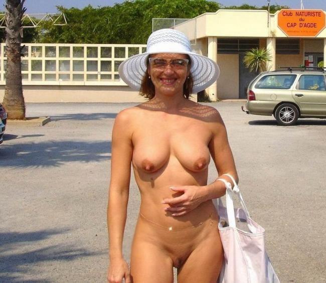 Голая тетка в шляпке стоит возле магазина.