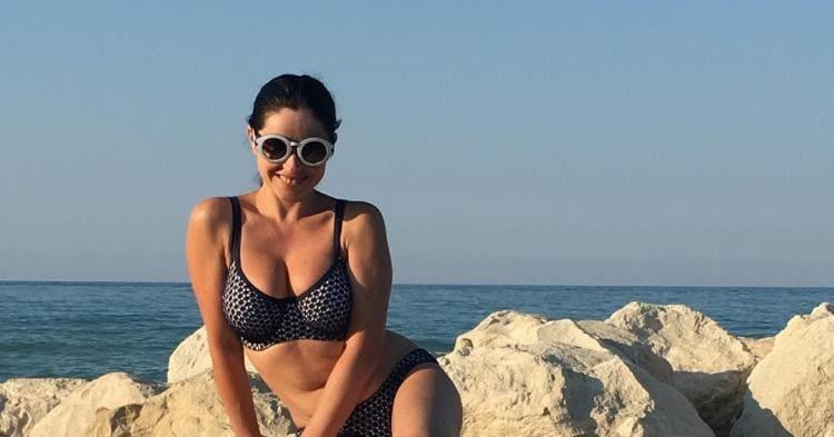 Любовь Тихомирова фото купальнике, в солнцезащитных очках улыбается сидит на скалах