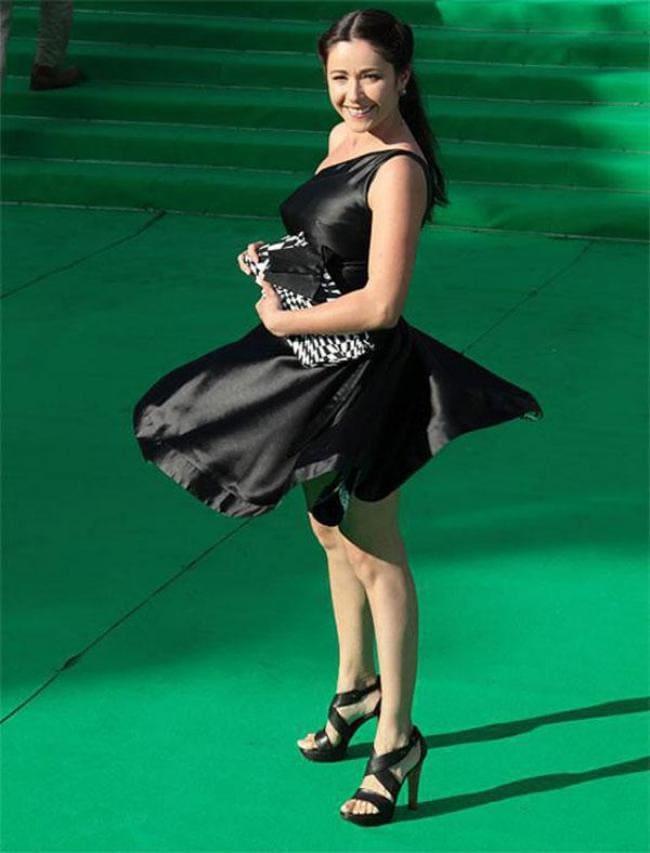 Черное платье ветер поднял юбку, босоножки на высоком каблуке черные.