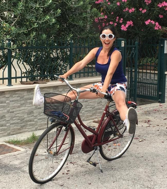 на велосипеде в ярких шортах раздвинула ноги.