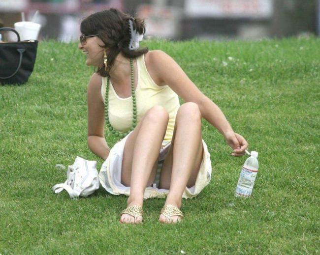 Сидит на траве ноги согнуты в коленях, видны трусы.