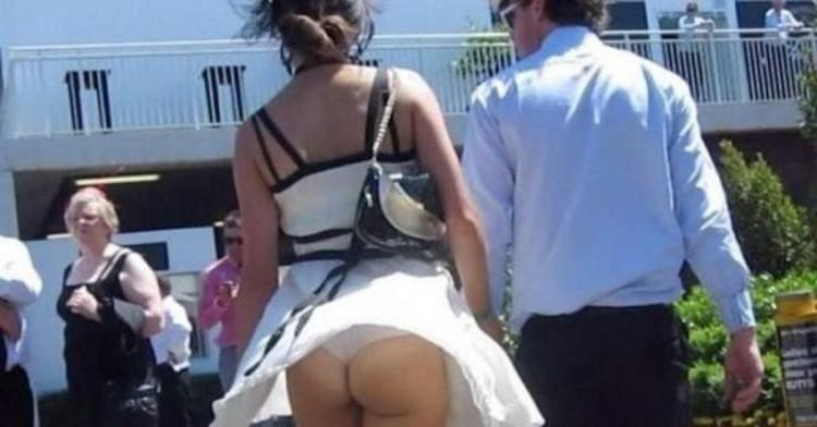 Ветер поднял юбку засветив попу и трусы.