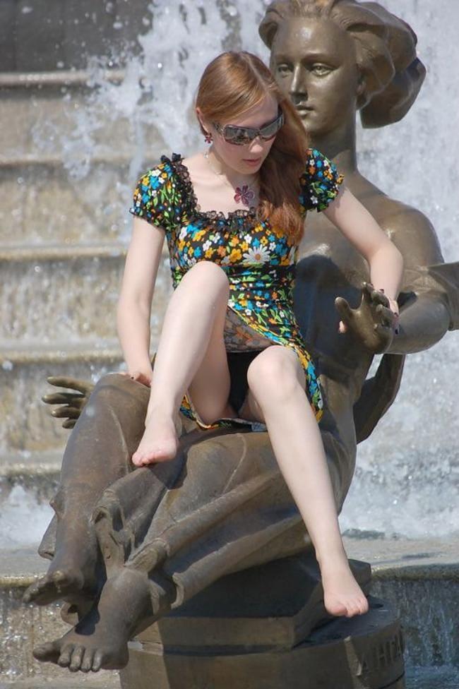 Сидит на статуе возле фонтана ножки ступни засвет трусиков.