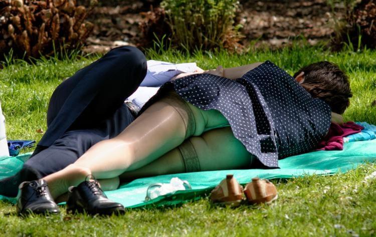 Лежит на покрывале на траве, в чулках засвет попы.