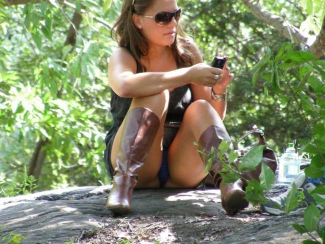 Сидит на попе в кустах в сапожках, показывая трусы.