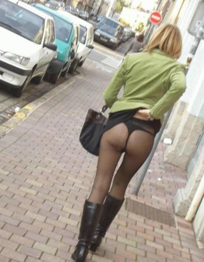 Идет по дороге чешет спинку задрав юбку оголив задницу в колготках и сапогах.